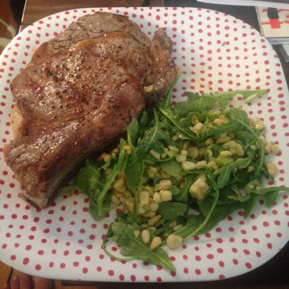Ribeye steak with a corn, avocado, arugula salad on some lovely child safe plates
